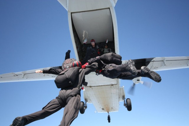 "Sgt. Kelly Becker, (left), the first female chaplain assistant to join the United States Army Special Operations Command Black Daggers parachute team, exits an aircraft during a jump. ""I was approached by my first sergeant before [physical training] one morning and he asked me if I wanted to go sky diving,"" Sgt. Kelly Becker, a chaplain assistant and United States Army Special Operations Command's Black Daggers team member said. He then proceeded to ask if she would be interested in sky diving as a job, and Becker excitedly said yes, the Vestal, N.Y., native explained."