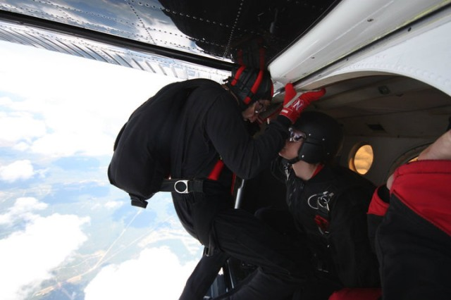 Sgt. Kelly Becker, (left), the first female chaplain assistant to join the United States Army Special Operations Command Black Daggers parachute team, readies to jump out of an airplane. The Black Daggers are a cumulative group of paratroopers from a diverse selection of jobs in USASOC. The Black Daggers conduct choreographed jumps out of helicopters, airplanes, into stadiums, fairs and events across the country from heights of up to 13,000 feet, but this is the first time in their history that a female chaplain assistant has joined their team.