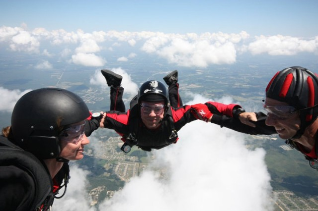 """Sgt. Kelly Becker (left), the first female chaplain assistant to join the United States Army Special Operations Command Black Daggers parachute team, jumps out of an airplane. """"I feel honored to be on the team with such elite soldiers and be to be the first chaplain assistant to do it,"""" the Vestal, N.Y., native said. The Black Daggers are a cumulative group of paratroopers from a diverse selection of jobs in USASOC."""