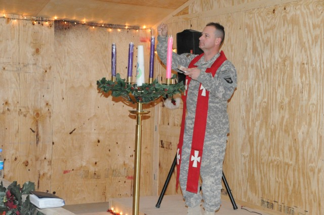 U.S. Army Chaplain (Maj.) Randal H. Robison of Grand Prairie, Texas, brigade chaplain for 4th Brigade Combat Team, 101st Airborne Division, lights the Advent candles during a Catholic Mass at the Frontline Chapel at Forward Operating Base Sharana Dec. 24.