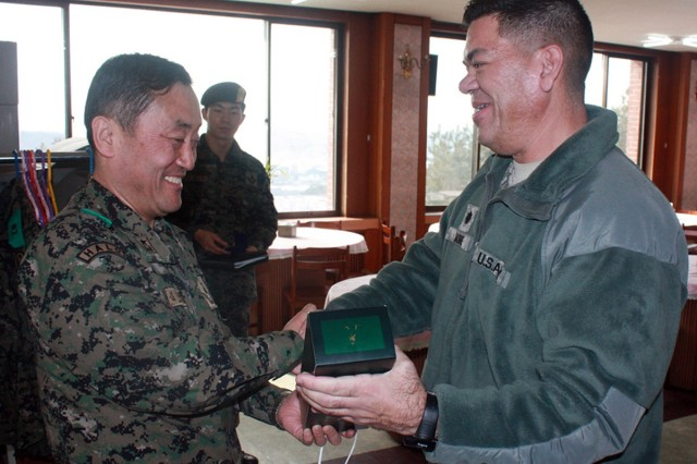 South Korean Special Warfare Training Group Commander Brig. Gen. Kim Nae-san and 6th Battalion, 52nd Air Defense Artillery Commander Lt. Col. William E. Darne exchange gifts during a visit Jan. 21.