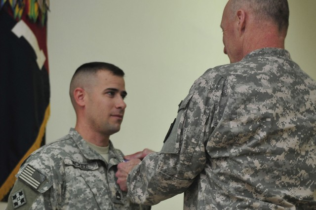 CONTINGENCY OPERATING SITE WARRIOR, Iraq - Lt. Gen. Robert Cone, deputy commanding general, operations, U.S. Forces-Iraq, presents the Purple Heart Award to Sgt. 1st Class Isaac McKee, platoon sergeant, Company B, 2nd Battalion, 12th Cavalry Regiment, 4th Advise and Assist Brigade, 1st Cavalry Division, during a ceremony at Contingency Operating Site Warrior, Iraq, Jan. 25, 2011. McKee, a native of New Braunfels, Texas, received the award for wounds sustained during an attack on his platoon, Dec. 26, 2010, while deployed as a part of the 1st Advise and Assist Task Force, 1st Infantry Division in support of Operation New Dawn.