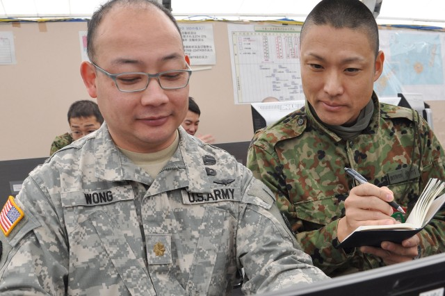 Maj. Manuel Sam Wong, a strategic intelligence officer, works with one of his Japanese counterparts Jan. 26, at Camp Kengun, Japan, during the start of Yama Sakura 59, an annual joint U.S. and Japanese training exercise intended to uphold relations between the two allied countries. Wong not only brought with him his military and technical expertise, but an authentic Elvis costume and wig to entertain U.S. and Japanese Soldiers when his free time allows. Wong is assigned to I Corps at Joint Base Lewis-McChord, Wash.