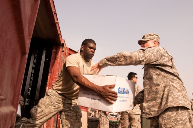 Pfc. Michael Hollingsworth (left) and First Sgt. Devin Horsley load a box into a container to be shipped back to Fort Riley, Kan., as their unit prepares to complete its year-long tour in Iraq this spring. Both Soldiers are assigned to Headquarters and Headquarters Company, Enhanced Combat Aviation Brigade, 1st Infantry Division.  (U.S. Army photo by Spc. Roland Hale, eCAB, 1st Inf. Div., PAO)