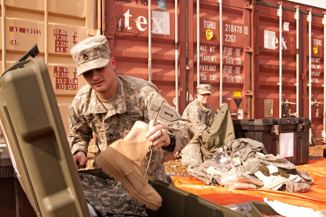 Staff Sgt. Kevin Beverly packs a box of personal equipment to be shipped back to Fort Riley, Kan., as his unit prepares to complete its year-long tour in Iraq this spring. Beverly is assigned to Headquarters and Headquarters Company, Enhanced Combat Aviation Brigade, 1st Infantry Division. (U.S. Army photo by Spc. Roland Hale, eCAB, 1st Inf. Div., PAO)