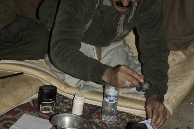 Maruf district Governor Abdul Samat Durrani, stamps a petition drawn up to request aid for farmers in eastern Kandahar province, Jan. 23, 2011. Durrani tries his best to address the needs of a remote district with no paved roads, no hospitals, and very little water.