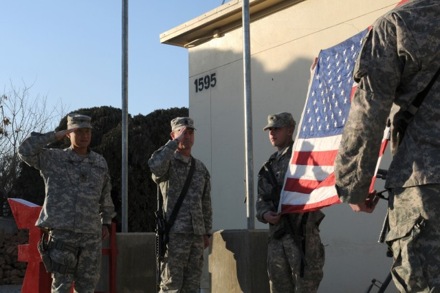 Col. Viet Luong, commander of the 3rd Brigade Combat Team, 101st Airborne Division and a resident of Fort Campbell, Ky., and Command Sgt. Maj. Gregory Patton, a resident of Fort Campbell, Ky., salute the World Trade Center flag on Jan. 24 at Forward Operating Base Salerno in Khowst Province, Afghanistan. The flag is carried by the 404th Civil Affairs Battalion, Airborne to different FOBs in Regional Command - East, Afghanistan to give Soldiers a chance to see the flag. The flag will be carried by the 404th for a year before being returned to Ground Zero, where it will be put in the Ground Zero Museum. (U.S. Army photo by Spc. Tobey White, Task Force Duke)