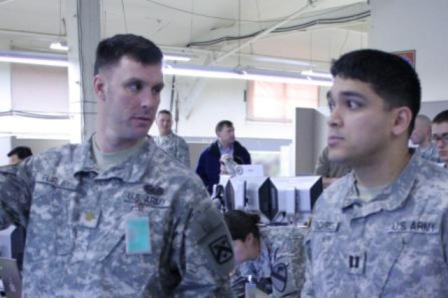 Maj. James Turley (left), an OPSGRP Alpha movement and maneuver observer/trainer, discusses current operations with a Joint Operations Center battle captain, Capt. Cesar Bacares, during the Mission Rehearsal Exercise at Fort Hood, Texas, Jan. 26.