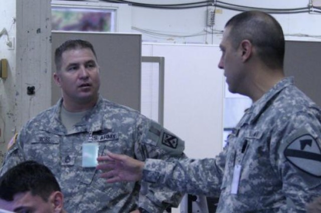 Sgt. 1st Class Richard Ross (left), an OPSGRP Alpha movement and maneuver observer/trainer, discusses operations with a 1st Cavalry Soldier on the exercise Joint Operations Center floor during the Mission Rehearsal Exercise at Fort Hood, Texas, Jan. 26.