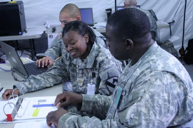 Lt. Col. James Wilkins (right), an OPSGRP Alpha senior logistics observer/trainer discusses logistical operations with Maj. Dee Jones, the 1st Cavalry Division maintenance officer, at the logistical cell near the Joint Operations Center during the Mission Rehearsal Exercise at Fort Hood, Texas, Jan. 25.