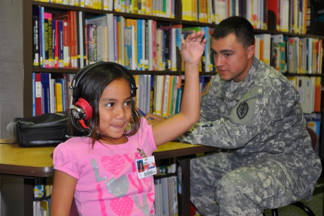 Private Stephen Charlie (right), a fire support specialist, Headquarters and Headquarters Company, 25th Combat Aviation Brigade, conducts an audio test on a student at Mililani Uka Elementary School, Jan. 26.  (Photo by Sgt. Daniel Schroeder I 25th Combat Aviation Brigade Public Affairs)