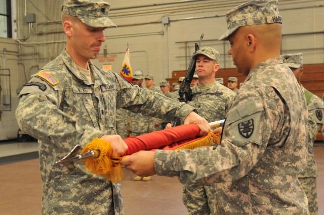 Lieutenant Col. Steven Wilke, (left) and Command Sgt. Maj. John Harris, (right) Special Troops Battalion command team, roll the battalion colors for casing during a deployment ceremony Jan. 28 at Fort Eustis' Anderson Field House. The STB will deploy to Afghanistan next month in support of overseas contingency operations. (U.S. Army photo by Sgt. Edwin J. Rodriguez)
