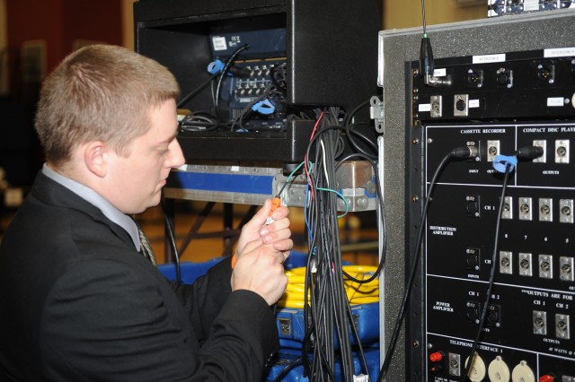 A White House Communications Agency employee prepares the audio mix position for a presidential event.