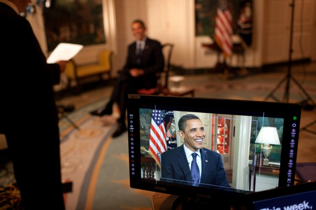 A White House Communications Agency employee helps President Barack Obama prepare for his weekly video address.