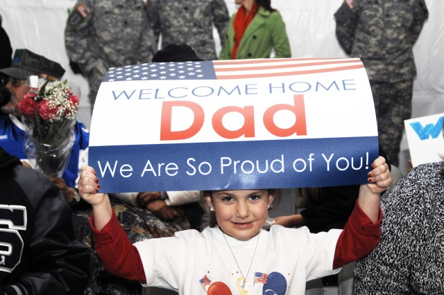 Hailey Tomaka, 5, holds up a sign while waiting for her father, Lt. Col. Paul Tomaka, at the welcome home ceremony for III Corps Soldiers held Jan. 28.