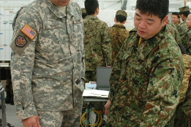 Chief Warrant Officer 4 Mario A. Torres and Maj. Seiichi Yokoyama look over a diagram during Yama Sakura 59, a command post exercise at Camp Kengun, Japan. Yokoyama and Torres found out during Yama Sakura 59 they have a lot in common - both speak English and Spanish. Yama Sakura is an annual, bilateral exercise with Japanese forces and the U. S. military.