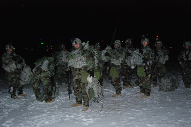 """""""Manchu Lightfighters"""" with 2-9th Inf., 1st HBCT, wait for the arrival of UH-60 Blackhawk helicopters during a night time air assault training exercise Dec. 9-10. The Manchus, along with crew members from 2nd Combat Aviation Brigade participated in Operation Iron Forge Lite at Rodriguez Live Fire Complex."""