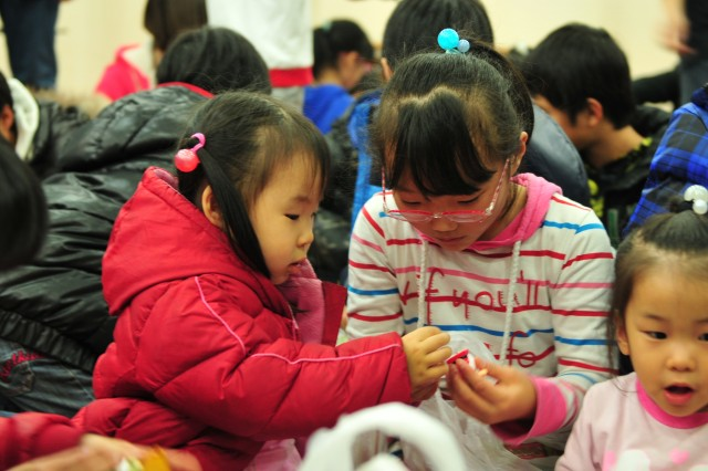 "Two girls play with the gifts they received from Santa during a 6-37th FA visit to ""House of Isaac,"" an orphanage located in Uijeongbu, on Dec. 21."