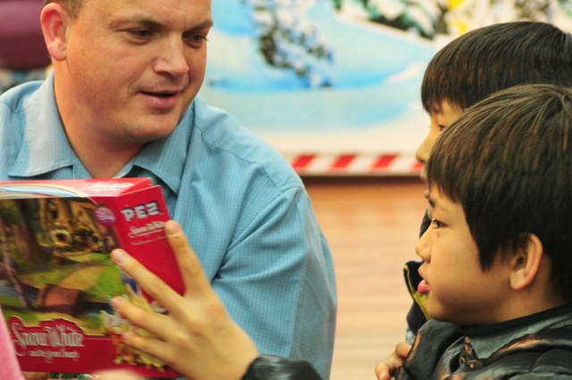 "A Soldier with C Battery, 6-37th FA, plays with two children during the unit's visit to ""House of Isaac,"" an orphanage located in Uijeongbu, on Dec. 21."