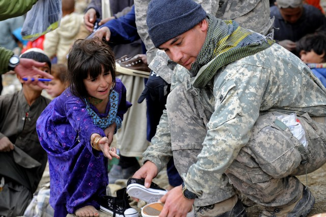 Sgt. 1st Class Manuel Delarosa, Provincial Reconstruction Team Zabul, Shinkai Detachment, finds a pair of shoes for a young girl while helping Afghan National Security Forces distribute winter supplies in Safidar village, Afghanistan, Feb. 1.