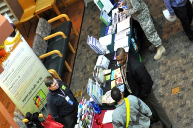 Soldiers take time to visit with staff and vendors during a fair of pain-management related information at the pain management conference at Madigan Healthcare System Jan. 31.