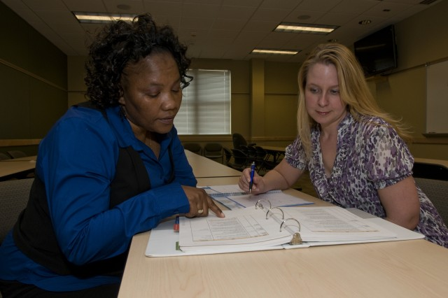 Jennifer Stevens, a Community Outreach Services Specialist, and Amanda Hammond, a Army Reserve School Support Specialist, look over a calendar of upcoming potential dates for Army Reserve Child, Youth and School Services events to support Reserve families in South Carolina, Tennessee and Alabama.