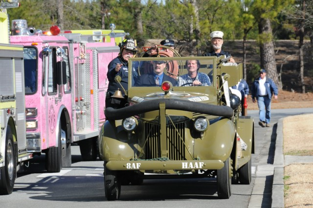 """Rags,"" the newly renovated 1941 Ford Fire Truck, arrives at the Mighty Eighth Air Force Museum Jan. 28 from Fort Stewart, where the renovation took place. Driving the vehicle is Allen Deloach, the lead paint and sheet mechanic from Fort Stewart's Directorate of Logistics, who was in charge of the restoration work. The fire truck resided at Hunter Army Airfield from 1941 to 1948 before purchased as military surplus by the Isle of Hope Volunteer Fire Department in Savannah. In 2000, they donated it to the Fort Stewart Museum, which has loaned Rags to the Mighty Eighth Museum, where it will remain."