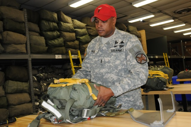 Chief Warrant Officer 4 Gene Moore checks the parachute packing job of one of his Soldiers. After 32 years in the Army, and 24 as a parachute rigger, he will retire July 1.
