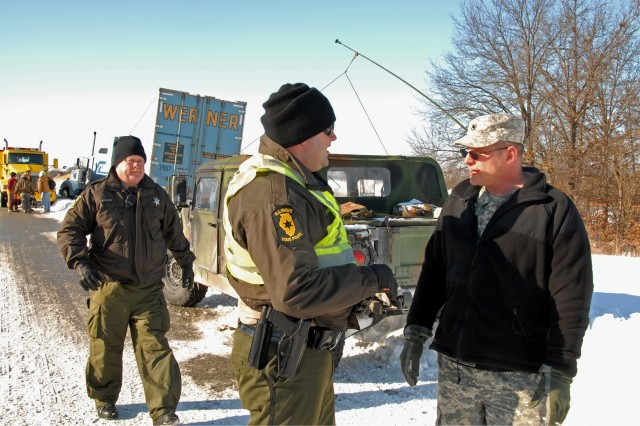 Staff Sgt. Rick Ensley of Quincy, with the 1844th Transportation Company based in Quincy, Ill., discusses an extraction plan with Illinois State Trooper Brandon Douglas, Feb. 2, on Interstate 72, near Pittsfield. The Illinois National Guard worked with troopers to assist stranded motorists after Gov. Pat Quinn called approximately 500 Guard members to state active duty for a winter weather emergency.
