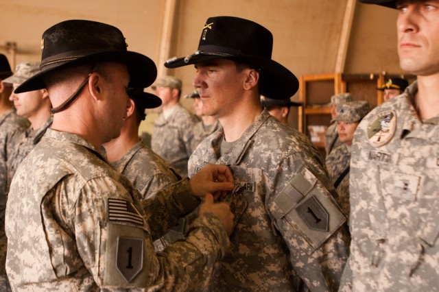 Lt. Col. Kenneth Chase, commander of the 1st Squadron, 6th Cavalry Regiment, Enhanced Combat Aviation Brigade, 1st Infantry Division, pins an Air Medal on the chest of Chief Warrant Officer 3 William Kearns during an end of tour award ceremony on Camp Taji, Iraq, Feb. 1. U.S. Army photo by Spc. Roland Hale, eCAB, 1st Inf. Div., PAO