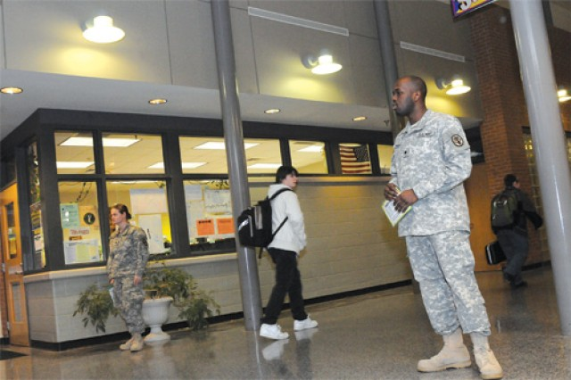 Fort Lee BOSS members Spc. Irina McQueen and Spc. Tim Harris stand in the hallway as students walk to class at JEJ Moore Middle School Jan. 19. McQueen and Harris are BOSS members who volunteer for the organizations' meet-and-greet program.