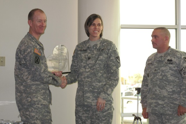 Capt. Steven McDaniel, chief of donor center operations at the Robertson Blood Center, presents the plaque for Top Large Unit blood donations to representatives from 36 Engineer Brigade, Capt. Elizabeth Walgren and Staff Sgt. William Thompson at the Robertson Blood Center at Fort Hood, Texas on Jan. 26, 2011.