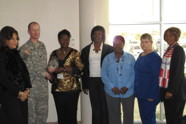 Capt. Steven McDaniel, chief of donor center operations at the Robertson Blood Center, presents an award to Adrienne Rias and ladies from AFGE for their Veterans Affairs blood drives on Jan. 26, 2011.