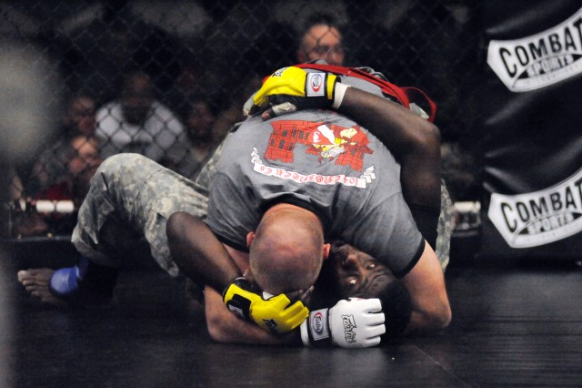 Specialist Nathaniel Brown, 4th Sustainment Brigade, subdues Spc. Warren Jackson, 4th Sust. Bde., Jan. 28 at Abrams Physical Fitness Center during the 2011 Fort Hood Combatives Championships.