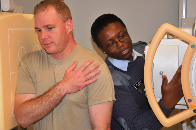Capt. Rosalind Asiedu (right) of the Ghana Air Force trains with Army Sgt. Eric Genge on taking X-rays of Genge's scapula, or shoulder blade, during a class at the Medical Education & Training Center.