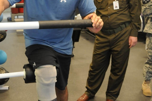 Iraqi army 2nd Lt. Wyam Musa instructs 1st Lt. Rahul Harpalani, with 4th Infantry Brigade Combat Team, 1st Infantry Division, how to correctly perform a rehabilitative exercise during a physical therapy session Feb. 2.  Harpalani received his leg prosthetic just six days prior to this session.