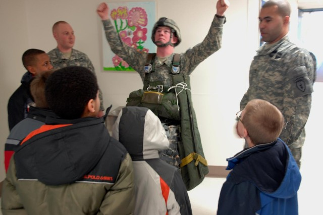 Sgt. 1st Class Tony Ayabarreno, center, a signal support systems specialist with 2nd Battalion, 377th Parachute Field Artillery Regiment, 4th Brigade Combat Team (Airborne), 25th Infantry Division, shows Orion Elementary School students how paratroopers control their parachutes. Ayaberreno and fellow paratroopers visited the school as part of a partnership program with the Anchorage School District allowing for servicemembers to volunteer at various schools.