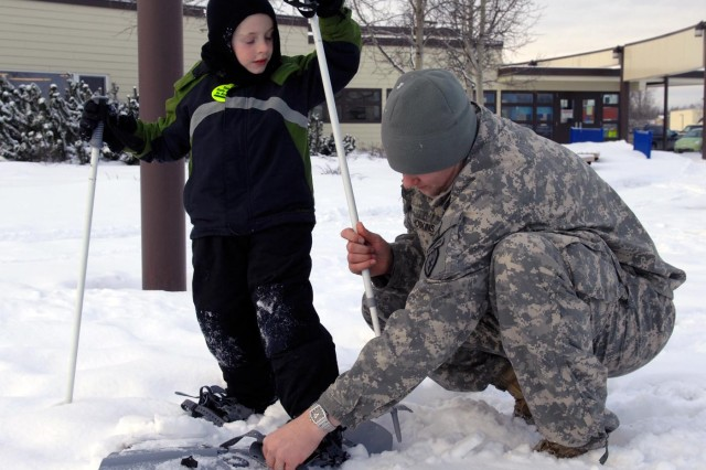 Chaplain (Capt.) Logan McCurdy, of 2nd Battalion, 377th Parachute Field Artillery Regiment, 4th Brigade Combat Team (Airborne), 25th Infantry Division, helps a student from Orion Elementary School into a pair of snow shoes, Jan. 21, during a demonstration of Army equipment as part of a partnership program with the Anchorage School District allowing for servicemembers to volunteer with various schools.