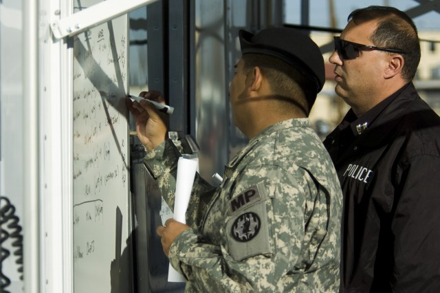 Capt. Robert Becerra, a Soldier with Fort Bliss' 93rd Military Police Battalion and a relief operations leader, along with a Directorate of Emergency Services officer, update action boards at the mobile command center outside Milam Athletic Center on the main post of Fort Bliss, Texas, Feb. 4. Milam served as the centerpiece of eight relief sites on post to aid military families after a mid-week storm battered utility grids throughout greater El Paso.