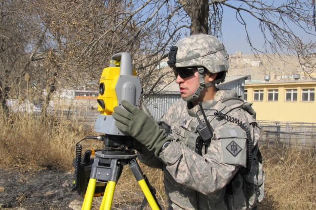 Sergeant Angel Santos, a surveyor from the Bronx, New York, aligns his laser-precise equipment to collect elevation data on a survey mission in Kabul.