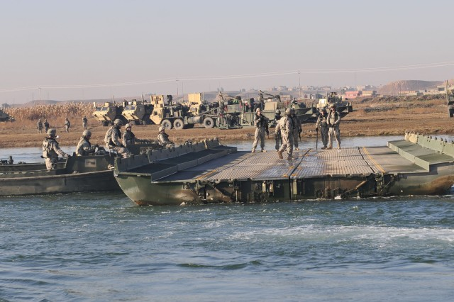 Soldiers assigned to 299th Engineer Company, 724th Engineer Battalion, 36th Engineer Brigade, use M2K Combat Bridge Boats to dismantle an Improvised Rafting Bridge on the Tigris River near Sharqat, Iraq, Jan. 23, 2011. They were able to dismantle the bridge because a new permanent bridge, built by Iraqi hands, opened to traffic for the first time, providing safe reliable transit to the region.