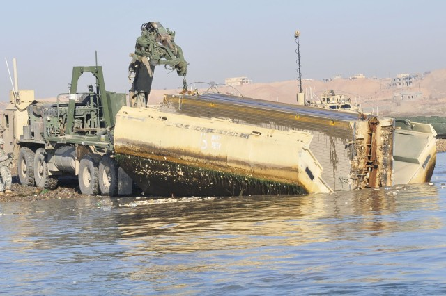 Soldiers assigned to 299th Engineer Company, 724th Engineer Battalion, 36th Engineer Brigade, Wisconsin National Guard, use a Heavy Expanded Mobility Tactical Truck to lift a piece of an Improvised Rafting Bridge out of the Tigris River during a bridge dismantling operation, near Sharqat, Iraq, Jan. 23, 2011.