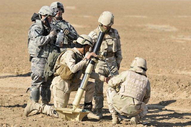 U.S. Soldiers of 1st Squadron, 9th Cavalry Regiment, 4th Advise and Assist Brigade, 1st Cavalry Division, supervise an Iraqi mortar crew from the 1st Battalion, 11th Brigade, 3rd Iraqi Army Division, during a live-fire exercise at Destiny Range in Ninewa province, Iraq, Jan. 25, 2011.