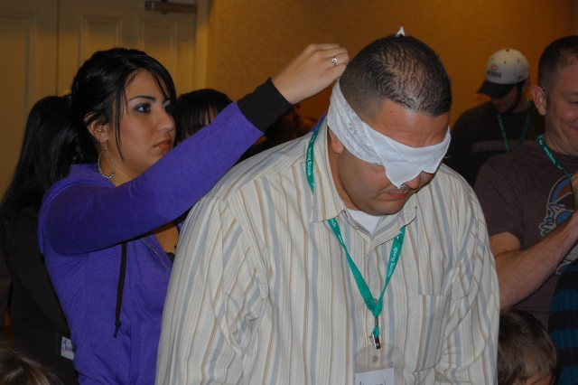 """Jaliz Jiminez ties a blindfold around the head of her father, Master Sgt. Manuel Jiminez, assistant inspector general of U.S. Army Medical Command, as they prepare to participate in a """"mine field"""" communication exercise at a Strong Bonds family enrichment retreat hosted by the 99th Regional Support Command Chaplain's office in Niagara Falls, N.Y., Jan. 28-30. The mine field exercise emphasized the importance of effective family communication during stressful situations, something Jiminez said his family needs to be intentional with.  (Photo by Sgt. Frank Vaughn)"""