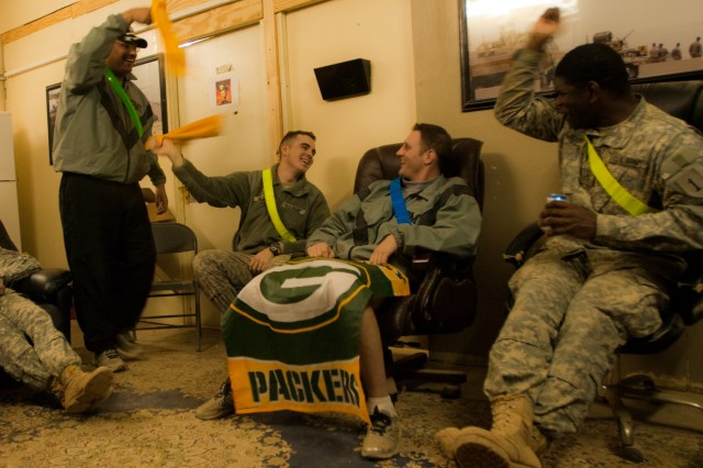 "Packers fan Capt. Adam Kirschling, center, sits back as fellow Soldiers wave their ""terrible towels"" in celebration of a Steelers touchdown. Kirschling and other Soldiers serving in Iraq with the Enhanced Combat Aviation Brigade, 1st Infantry Division gathered in small groups on Camp Taji to watch the Super Bowl, Jan. 7, via a live broadcast at 3 a.m. local time. U.S. Army photo by Spc. Roland Hale, eCAB, 1st Inf. Div., PAO"