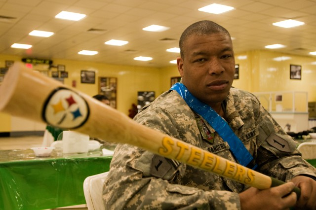 Chief Warrant Officer 2 Titus Sanders, a Steelers fan and pilot deployed to Iraq with the Enhanced Combat Aviation Brigade, 1st Infantry Division, holds up a piece of Pittsburgh gear while watching the Super Bowl on Camp Taji, Iraq. Soldiers on Camp Taji watched the game at 3 a.m. local time Jan. 7 via a live broadcast from the American Forces Network. U.S. Army photo by Spc. Roland Hale, eCAB, 1st Inf. Div., PAO