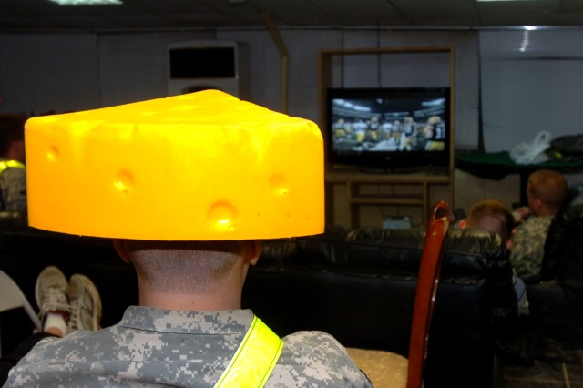 "Spc. Michael Johnson, deployed to Camp Taji, Iraq, with B Company, 601st Aviation Support Battalion, Enhanced Combat Aviation Brigade, 1st Infantry Division, sports a ""cheesehead"" while watching a live broadcast of the Super Bowl at 3 a.m. local time Jan. 7 on the American Forces Network. U.S. Army photo by Sgt. 1st Class Jeff Troth, eCAB, 1st Inf. Div., PAO"