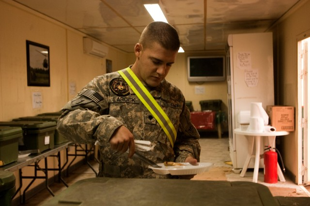 Spc. Timothy Larock prepares a meal inside the Guardian Café on Camp Taji, Iraq, Feb. 8. The café feeds Soldiers of the Enhanced Combat Aviation Brigade, 1st Infantry Division who cannot make it to the camp's main dining facility during their duty days. U.S. Army photo by Spc. Roland Hale, eCAB, 1st Inf. Div., PAO