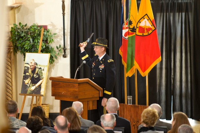 "Newly frocked Brig. Gen. Ted Martin dons his ""dusty"" Stetson and raises a Colt 44 during his frocking ceremony Friday at the Benning Conference Center. Beside the podium is a photo of Martin's father, retired Lt. Col. Ephriam Martin, who died in 1989. Martin is one of four brothers who followed in his father's footsteps."
