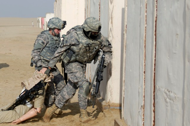CAMP BUEHRING, Kuwait - Pvt. Shelby Bandy (left) and Spc. Bryen Reid, both with the personal security detachment, Headquarters and Headquarters Troop, 3rd Advise and Assist Brigade, 1st Cavalry Division, move a casualty to a secure location during training on Camp Buehring, Kuwait  Feb. 8.